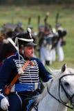Reenactor klädde, som den ryska soldaten för det Napoleonic kriget rider en häst Arkivfoto