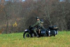 A reenactor rides a retro motorbike. Stock Photo