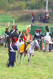 Reenactor si è vestito come il soldato di guerra napoleonica monta un cavallo Immagine Stock