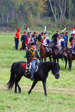 Reenactor si è vestito come il soldato di guerra napoleonica monta un cavallo Immagini Stock