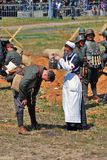A reenactor woman (nurse) pours water on the head of a soldier Stock Photos