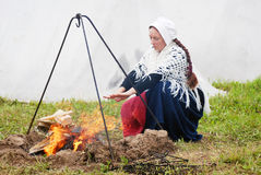 Reenactor woman warming his hands by the fire Royalty Free Stock Photography