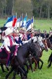 Reenactors拿着旗子的乘驾马 免版税库存图片