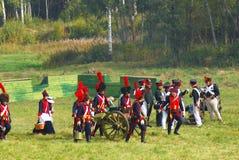 Reenactors穿戴了,拿破仑式的战争战士支持大炮 免版税库存图片
