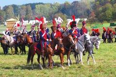 Reenactors穿戴了,拿破仑式的战争战士骑马 免版税库存图片