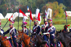 Reenactors穿戴了,拿破仑式的战争战士骑马 免版税库存照片