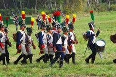 Reenactors穿戴了,拿破仑式的战争拿着枪的战士行军 免版税库存图片