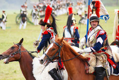 Reenactors dressed as Napoleonic war French soldiers ride horses Royalty Free Stock Photo