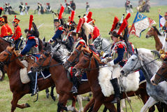 Reenactors dressed as Napoleonic war French soldiers ride horses Royalty Free Stock Images