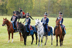 Reenactors dressed as Napoleonic war Russian soldiers ride horses Royalty Free Stock Images
