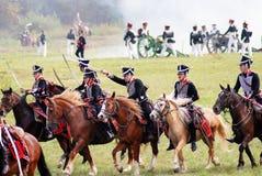 Reenactors dressed as Napoleonic war soldiers attack. MOSCOW REGION - SEPTEMBER 07, 2014: Reenactors dressed as Napoleonic war soldiers ride horses and attack Stock Image