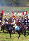 Reenactors dressed as Napoleonic war soldiers hold flags Royalty Free Stock Images