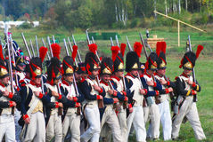 Reenactors dressed as Napoleonic war soldiers march holding guns. MOSCOW REGION - SEPTEMBER 07, 2014: Reenactors dressed as Napoleonic war soldiers march holding Stock Images