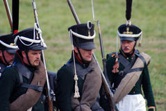 Reenactors dressed as Napoleonic war soldiers march holding guns Royalty Free Stock Image