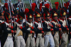 Reenactors dressed as Napoleonic war soldiers march holding guns Royalty Free Stock Photo