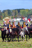 Reenactors dressed as Napoleonic war soldiers ride horses Royalty Free Stock Photo