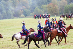 Reenactors dressed as Napoleonic war soldiers ride horses Royalty Free Stock Photography