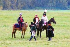 Reenactors dressed as Napoleonic war soldiers ride horses Stock Photo