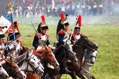 Reenactors dressed as Napoleonic war soldiers ride horses Royalty Free Stock Images