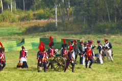Reenactors dressed as Napoleonic war soldiers stand by a cannon Royalty Free Stock Images