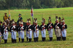 Reenactors dressed as Napoleonic war soldiers stand holding guns Royalty Free Stock Images