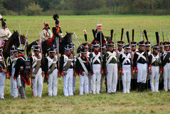 Reenactors dressed as Napoleonic war soldiers stand holding guns Stock Image