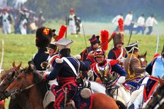 Reenactors fight and ride horses. Royalty Free Stock Image