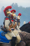 Reenactors in golden helmets ride horses Royalty Free Stock Image