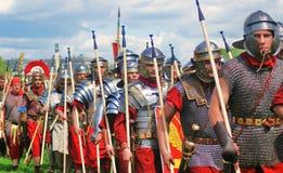 Reenactors kleidete wie der Soldatmarsch an, der Stangen hält Stockbild