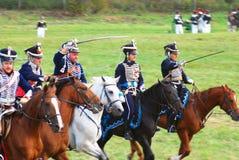Reenactors kleidete an, wie russische Soldaten des napoleonischen Krieges Pferde reiten Stockfoto