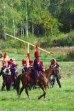 Reenactors kleidete an, wie Soldaten des napoleonischen Krieges Pferde reiten Stockfotografie