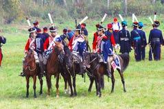 Reenactors kleidete an, wie Soldaten des napoleonischen Krieges Pferde reiten Stockbild