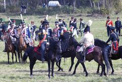 Reenactors kleidete an, wie Soldaten des napoleonischen Krieges Pferde reiten Stockbilder