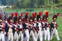 Reenactors s'est habillé comme marche de soldats de guerre napoléonienne tenant des armes à feu Images stock