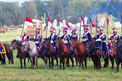 Reenactors si è vestito come i soldati di guerra napoleonica montano i cavalli Fotografia Stock