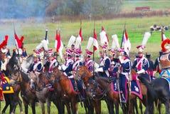 Reenactors si è vestito come i soldati di guerra napoleonica montano i cavalli Immagine Stock
