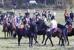 Reenactors si è vestito come i soldati di guerra napoleonica montano i cavalli Immagini Stock