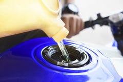 Reenchimento do óleo da motocicleta ao tanque fotografia de stock