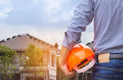 Resident engineer holding yellow safety helmet at new home building. Reent engineer holding yellow safety helmet at new home building under construction site Royalty Free Stock Image