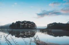 Refection острова и кустарников соснового леса на озере на зоре с волшебством неба и части 2 облаков стоковая фотография rf