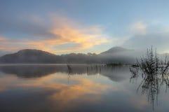Refection острова и кустарников соснового леса на озере на зоре с волшебством неба и части 4 облаков стоковое изображение