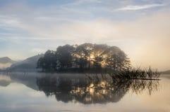 Refection острова и кустарников соснового леса на озере на зоре с волшебством неба и части 8 облаков стоковая фотография