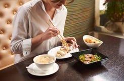 Refeição pedindo da mulher moreno no restaurante japonês luxuoso fotografia de stock