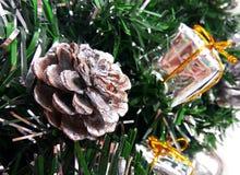 Refeições matinais artificiais da árvore de Natal decoradas com quinquilharia de prata, as caixas do brinquedo e o cone atuais fotos de stock