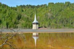 Refelction della torre di chiesa nel lago di Geamana nelle montagne di Apuseni, Romania Fotografie Stock