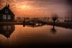 Sunrise on the Zaanse Schans. Refelction of the red sky on the water with the landmark bridge and windmill in Zaanse Schans, the Netherlands royalty free stock photo