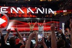 A referência aumenta os braços de Seth Rollins enquanto comemora com vitória dos fãs Imagens de Stock Royalty Free