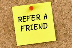 Refer a friend PostIt Note Pinned To Cork Board or corkboard. Refer a friend PostIt Note Pinned To corkboard stock photo