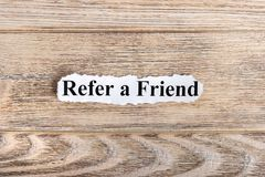 REFER A FRIEND text on paper. Word REFER A FRIEND on torn paper. Concept Image Royalty Free Stock Images