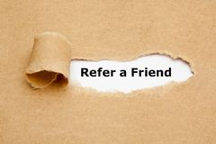 Refer a Friend Torn Paper. The text Refer a Friend appearing behind torn brown paper. Referral marketing concept royalty free stock photography